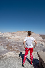 Fit attractive active woman looks out onto the Blue Mesa Trail at the Petrified Forest National Park in the Arizona Desert. Woman is wearing leggings and white t-shirt