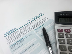 A pen, a calculator and a HMRC Stamp Land Duty Tax Form