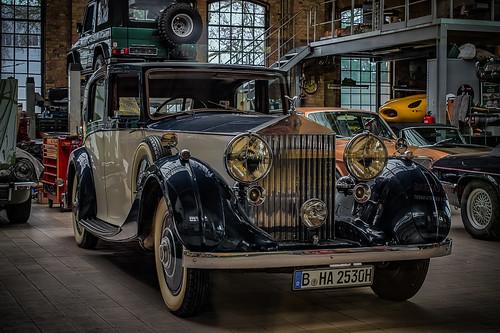 a wonderful old classic Rollce Royce in a workshop