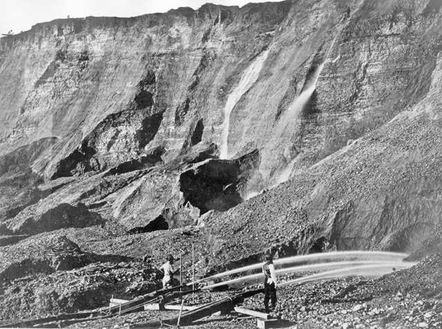 View of gold miners excavating an eroded bluff with jets of water at a placer mine in Dutch Flat, California, between 1857 and 1870