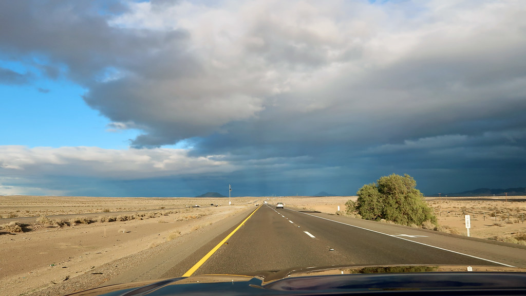 Beams of sunlight penetrating storm clouds and illuminating the Mojave Desert
