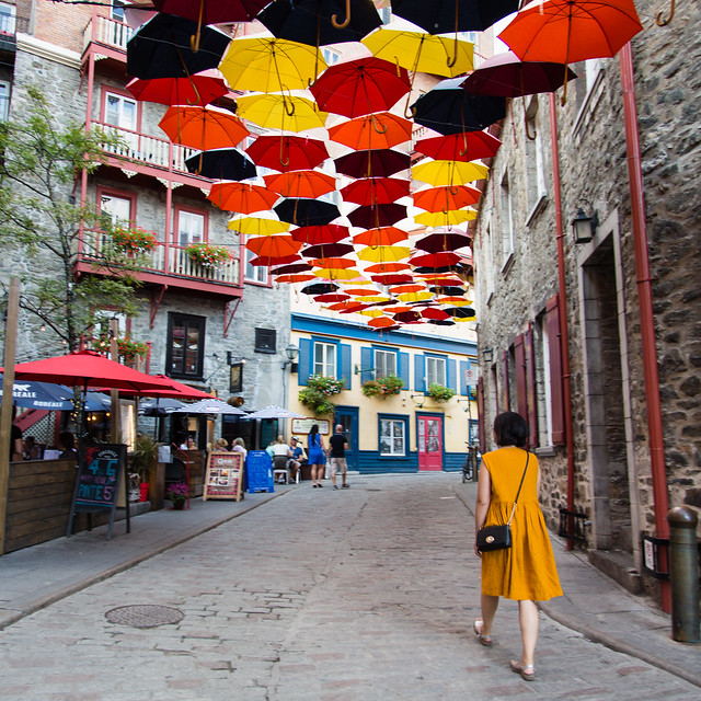 Walking down a little street with lots of umbrellas