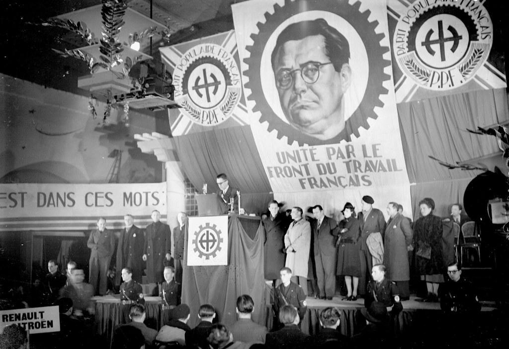 1942. Делегация представителей Рено-Ситроен под огромным портретом Жака Дорио в окружении символов Французской народной партии