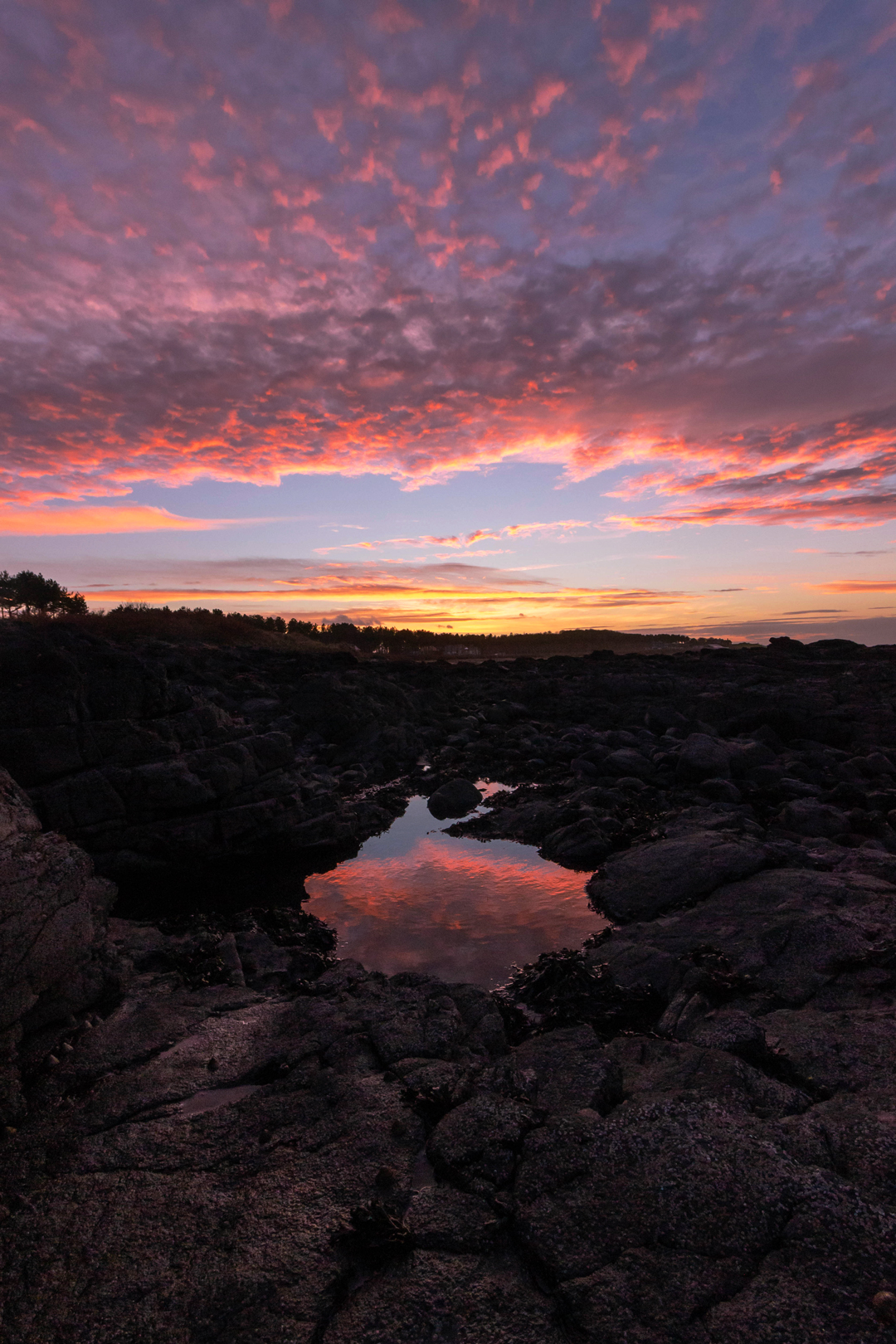 Sunset reflection in a rockpool at Yellowcraig Beach, East Lothian