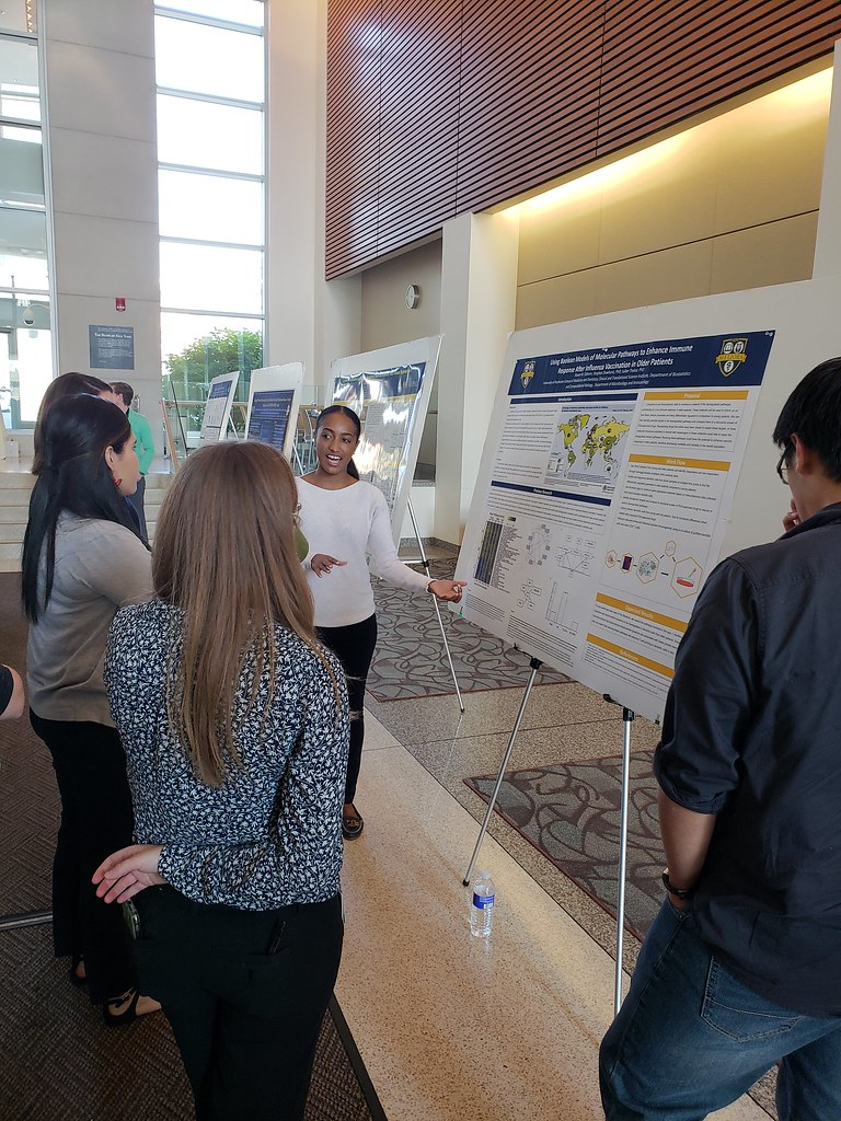 Raven Osborn explains her research on influenza to an interested group of individuals