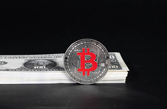 Silver Bitcoin with stack of money