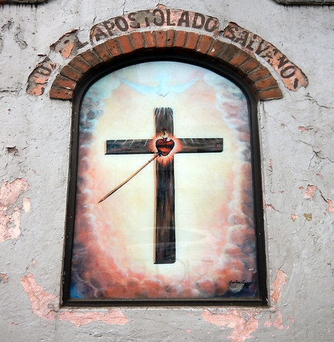 Decaying plaster wall with a mural of a cross in San Angel, Mexico