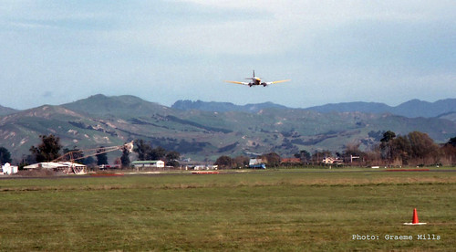 1987 Bruce Thompson in Douglas DC3 ZK-BBJ doing a beat up at Gisborne Airport after dropping the last load before departing for the final time to Milson. The loader for the aircraft can be seen to the left, 5 May 1987..