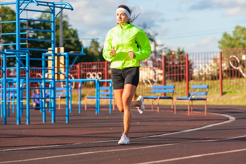 Jogging Concepts. Portrait of Professional Female Runner During Training. Running on Track and Equipped in Summer Training Outfit While Running.