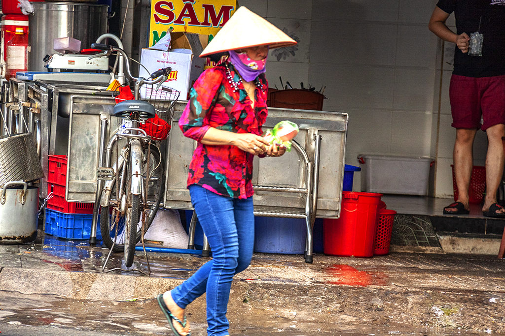 Woman wearing conical hat and jeans--Saigon