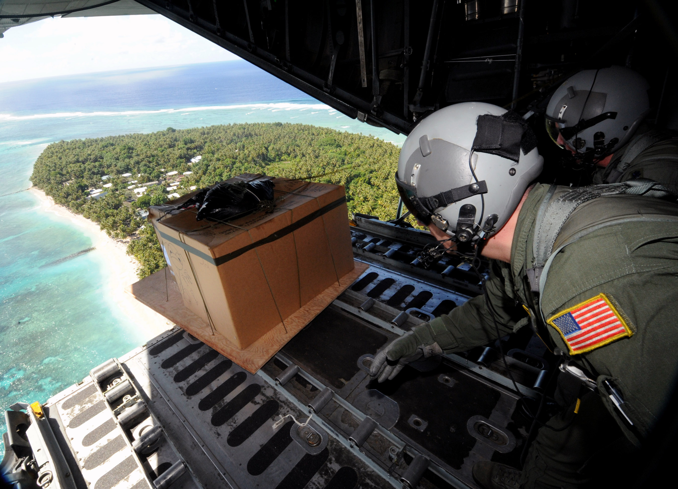 Tech. Sgt. Heath Bahyi and Chief Master Sgt. Michael Sundberg push out a boxed pallet of donated goods over the remote Island of Yap from a C-130 Hercules, Dec. 19 during Operation Christmas Drop. Airmen today continue the tradition, delivering supplies to remote islands of the Commonwealth of the Northern Marianas Islands, Yap, Palau, Chuuk and Pohnpei. In all, more than 180 boxes were built for the humanitarian mission, making 2008 one of the largest drops in Operation Christmas Drop's 57 year history. Both are loadmasters from the 36th Airlift Squadron, Yokota AB, Japan. (U.S. Air Force photo/ Master Sgt. Kevin J. Gruenwald) released..
