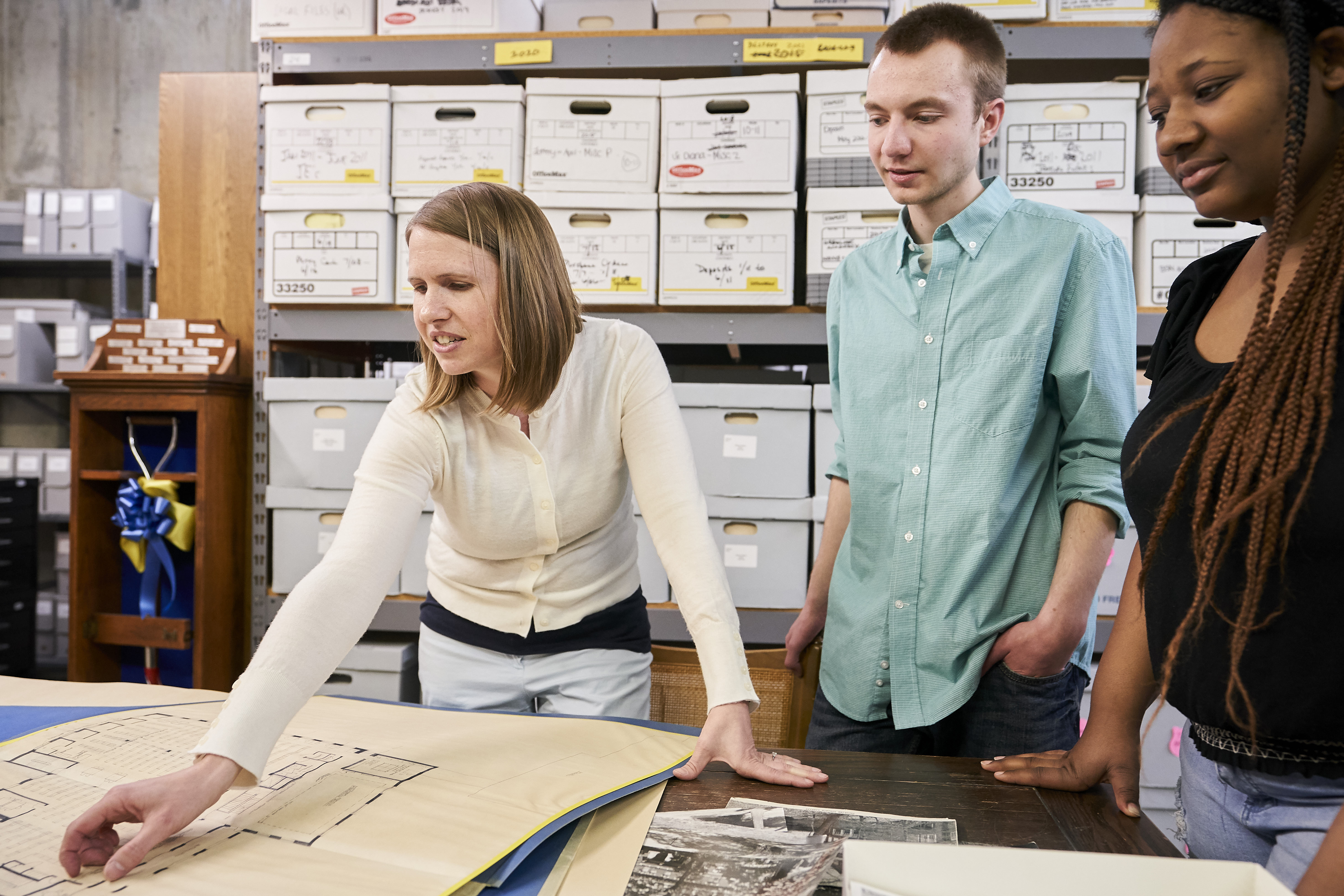 Archivist shows students original floor plans of library