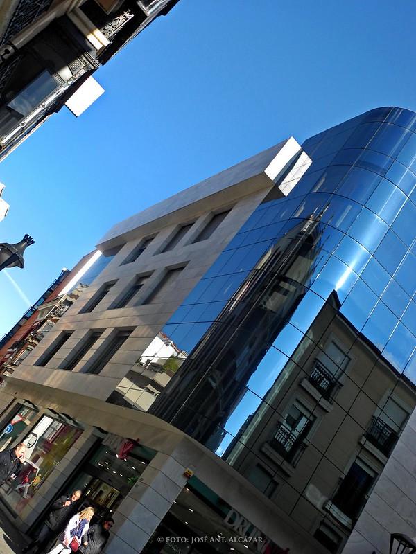 Edificio con reflejos en la fachada de cristal, con encuadre inclinado