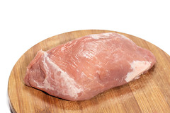 Slice of raw pork meat on the cutting board