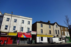 """A terrace of six three-storey shops seen on a sunny day.  A gap in the middle of the terrace offers access to the backs.  Signs above the shops read """"Premier Express"""", """"Ellalan Convenience Store"""", """"Peri Pizza"""", and """"Lobo Seafood Ltd""""."""