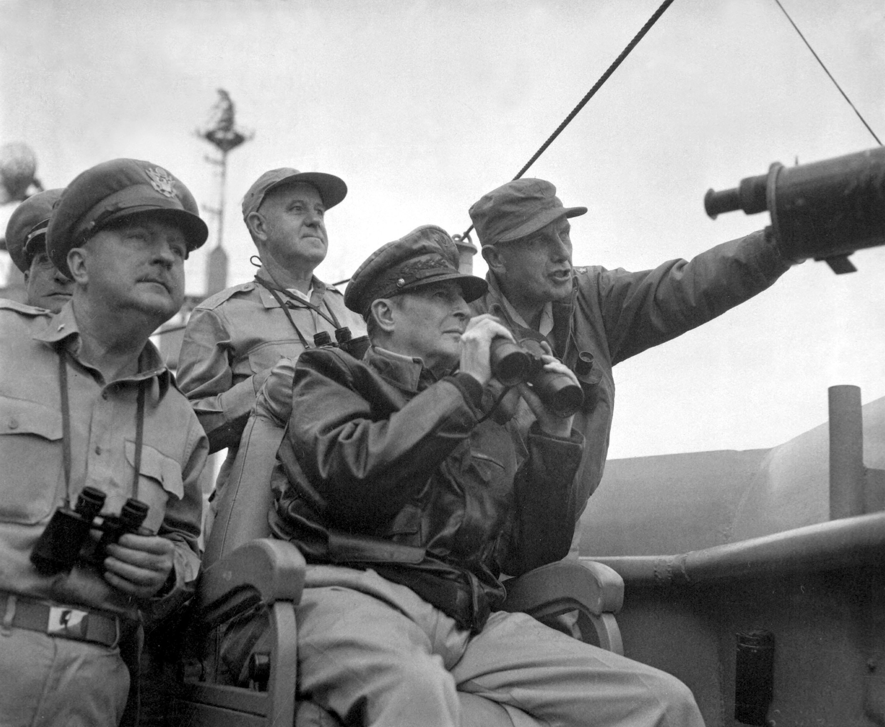 Brigadier General Courtney Whitney; General Douglas MacArthur, Commander in Chief of U.N. Forces; and Major General Edward M. Almond observe the shelling of Inchon from the USS. Mt. McKinley, September 15, 1950. Nutter (Army).NARA FILE #: 111-