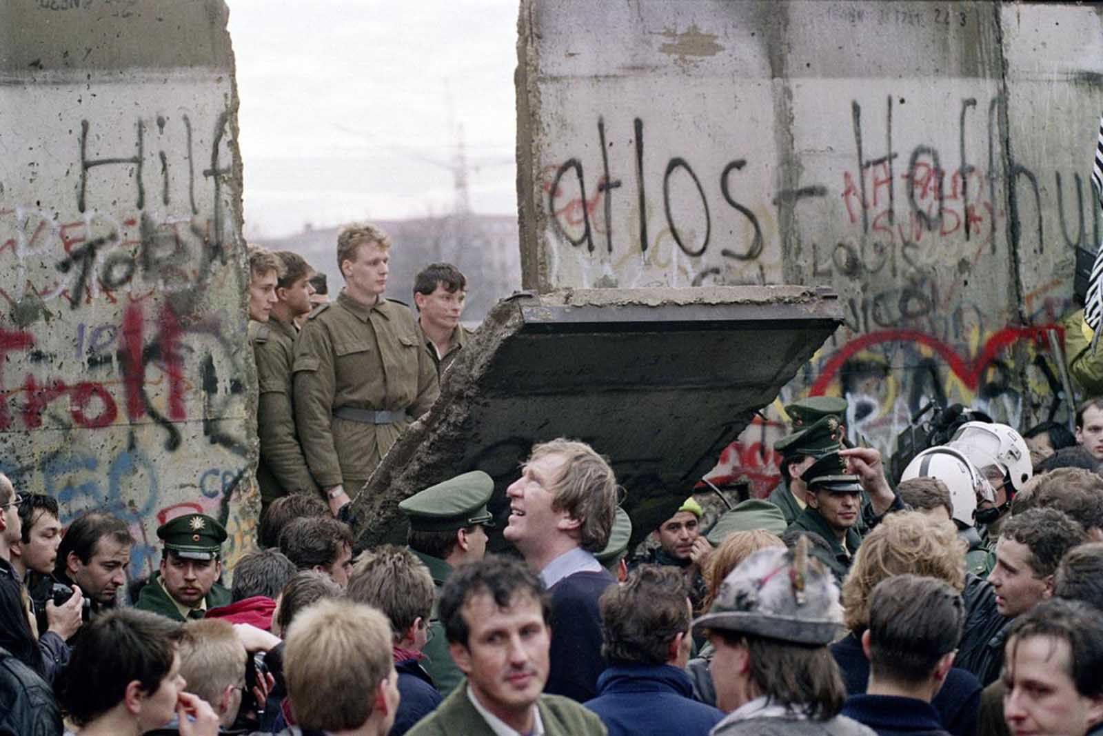 .West Berliners crowd in front of the Berlin Wall early on the morning of November 11, 1989, as they watch East German border guards demolishing a section of the wall in order to open a new crossing point between East and West Berlin, near Potsdamerplatz.
