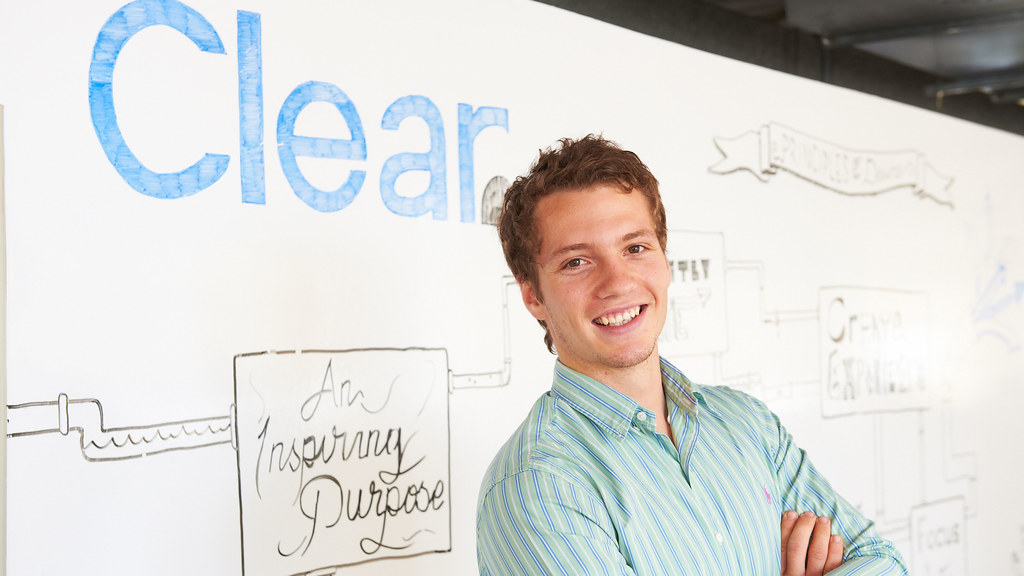 Photo of Joseph Sherlock standing in front of a display with the text 'Clear'