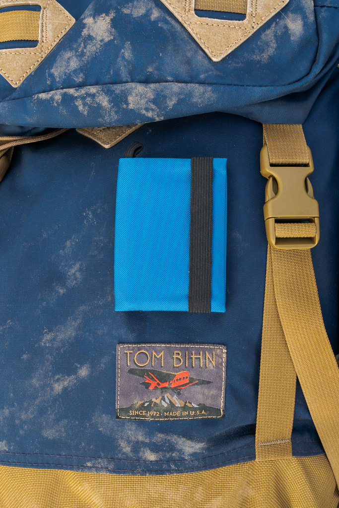 My Tom Bihn Nik's Minimalist Wallet sits on top of my dusty Tom Bihn Guide's Pack
