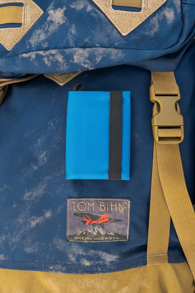 My Tom Bihn Nik's Minimalist Wallet sits on top of my dusty Tom Bihn Guide's Pack