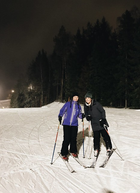 Two people posing in skis at the top of a snow covered hill.