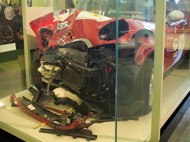 smashed remains of a red car presented in a museum display