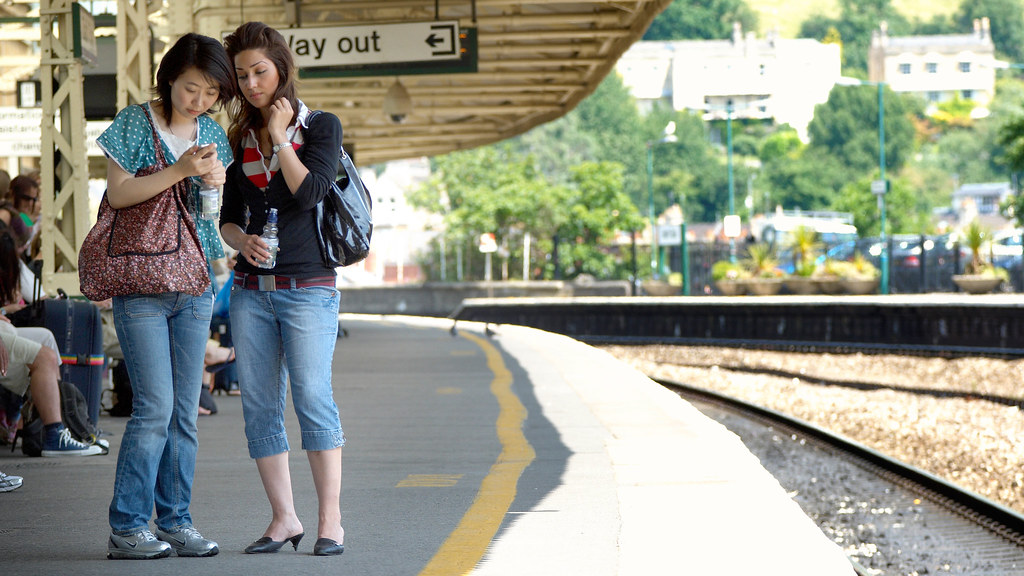 Two students standing on the platform at Bath Spa train station