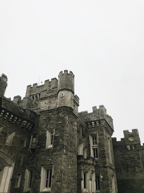 The corner of a grey-stone castle with multiple towers and windows.