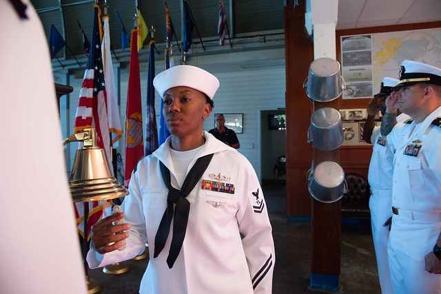 PEARL HARBOR (Nov. 11, 2018) Operations Specialist 2nd Class Dominique Cannon, from Dallas, Texas, tolls 21 bells during a World War I commemoration ceremony celebrating Armistice and Veterans Day at the Pacific Fleet  Boathouse. Armistice Day is commemorated every year in honor of the temporary cease fire between the Allied nations and Germany which went into effect on the eleventh hour of the eleventh day of the eleventh month on November 11, 1918 seven months prior to the signing of the Treaty of Versailles. The world's largest fleet command, the U.S. Pacific Fleet encompasses 100 million square miles, nearly half the Earth's surface, from Antarctica to the Arctic circle and from the West Coast of the United States into the Indian Ocean. The U.S. Pacific Fleet consists of approximately 200 ships/submarines, nearly 1,200 aircraft, and more than 130,000 Sailors and civilians.. (U.S. Navy photo by Mass Communication Specialist 2nd Class Kenneth Rodriguez Santiago/Released)