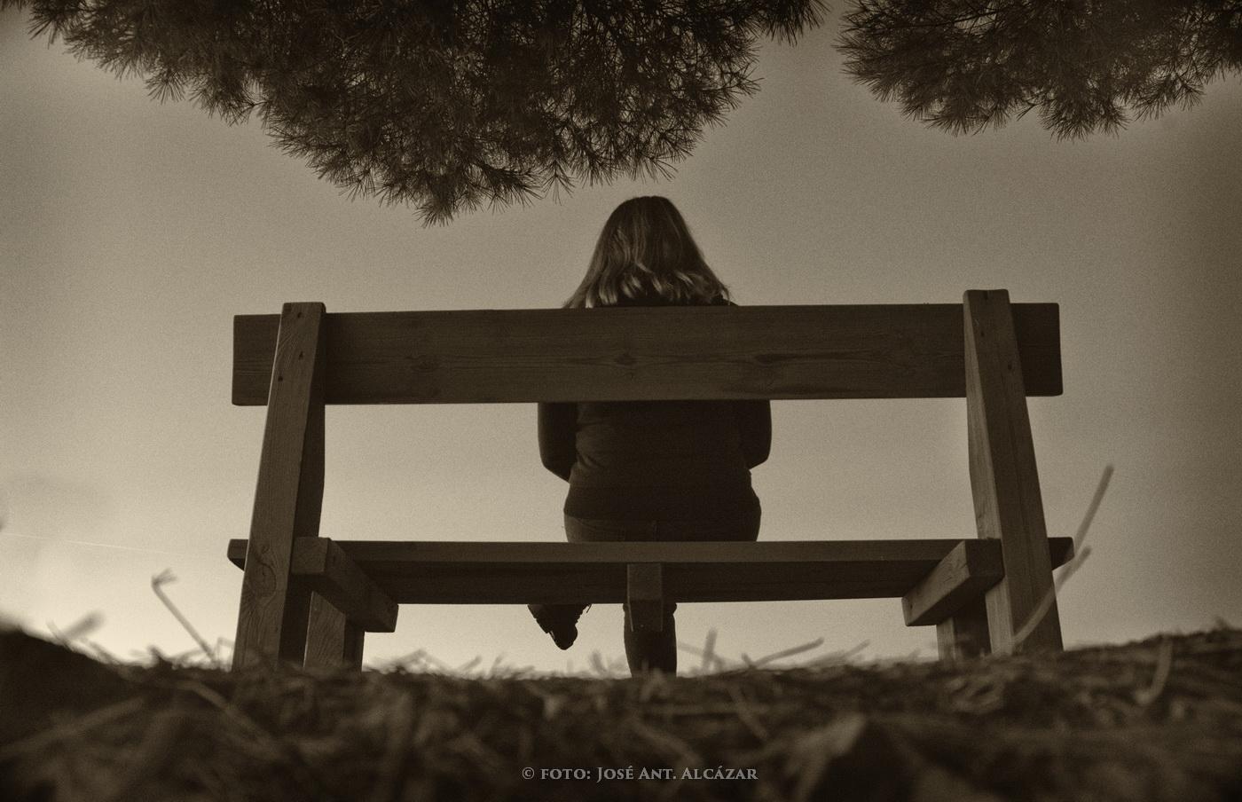 Foto en blanco y negro, con virage sepia, de una chica de espaldas, sentada en un banco.
