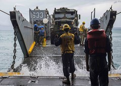 Boatswain's Mate 3rd Class Nayyaamunhotep Stubbs signals for a landing craft, utility (LCU) to approach USS Ashland (LSD 48) while onloading equipment in Okinawa earlier this week. (U.S. Navy/MC2 Joshua Mortensen)