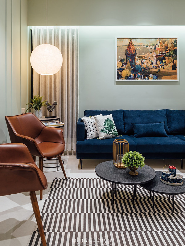 A living room in navy blue sofa, leather chairs, patterned monochrome rug  and heavy upholstery