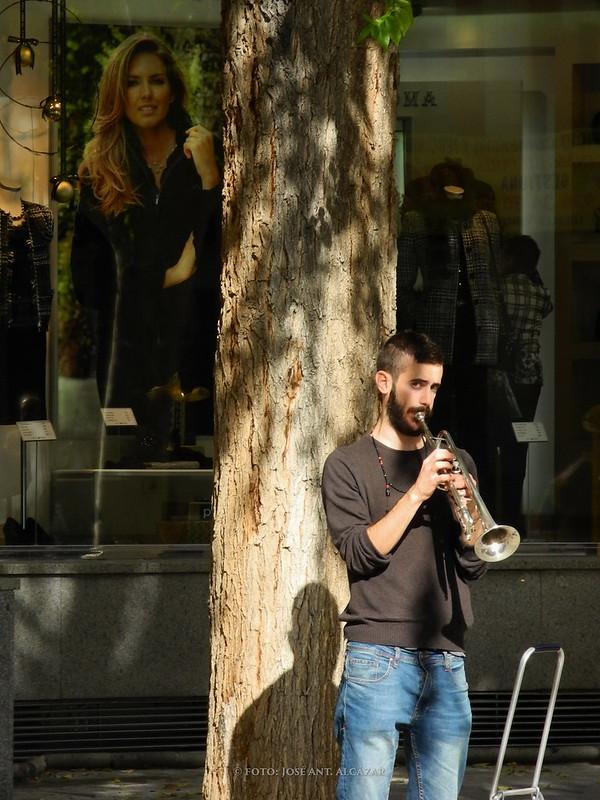Músico callejero tocando la trompeta al lado de un árbol, en el fondo foto de modelo en un comercio