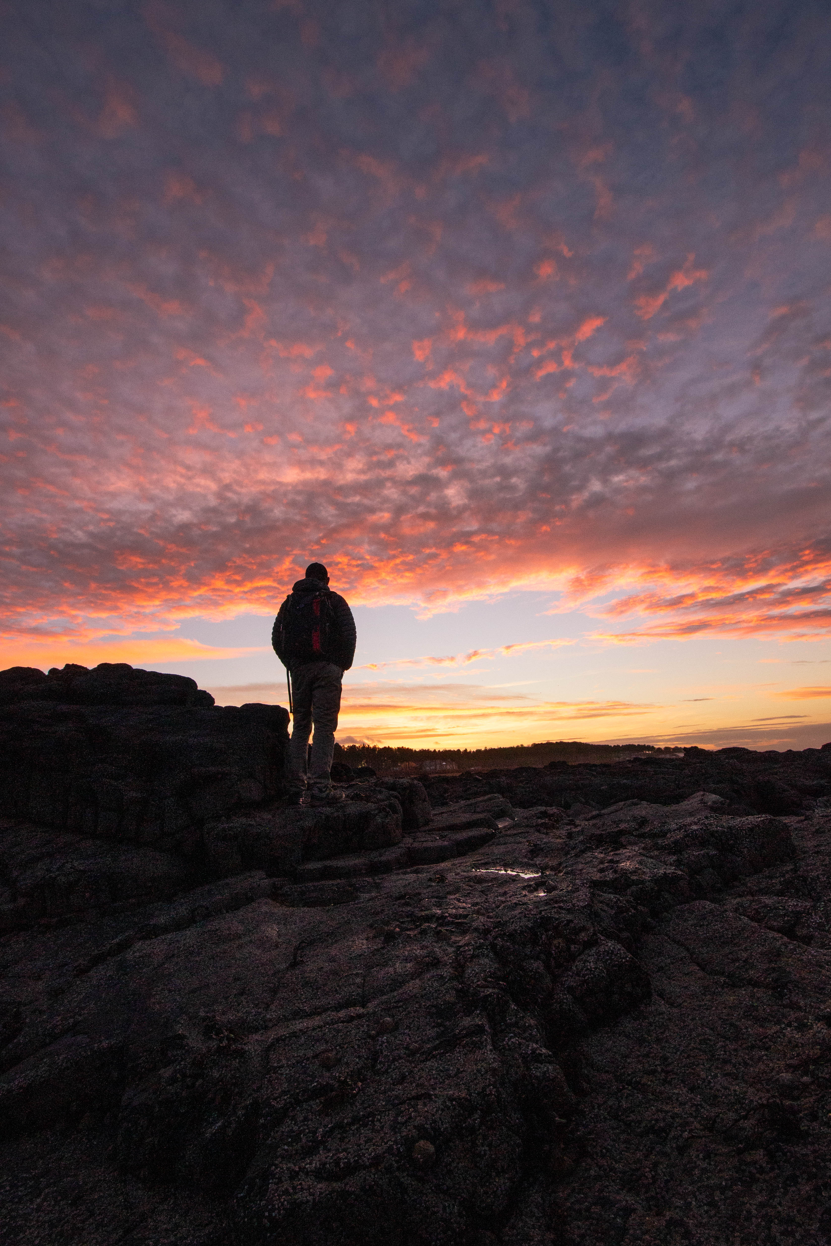 Silhouette of a person against a vibrant sunset at Yellowcraig Beach