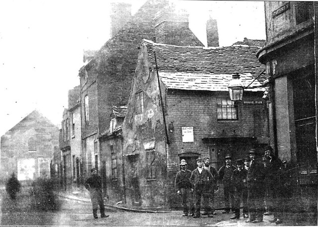 A crowd of men lounge a few yards from the rear entrance of the Brown Bear in Little Berry Street. In front of them, on the corner of Stafford Street and Horse Fair stands the Black Horse.