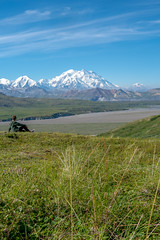 Young adult woman sits on a hill looking out at Mount Denali (McKinley) in Denali National Park. Concept for thinking, peaceful, nature, exploring
