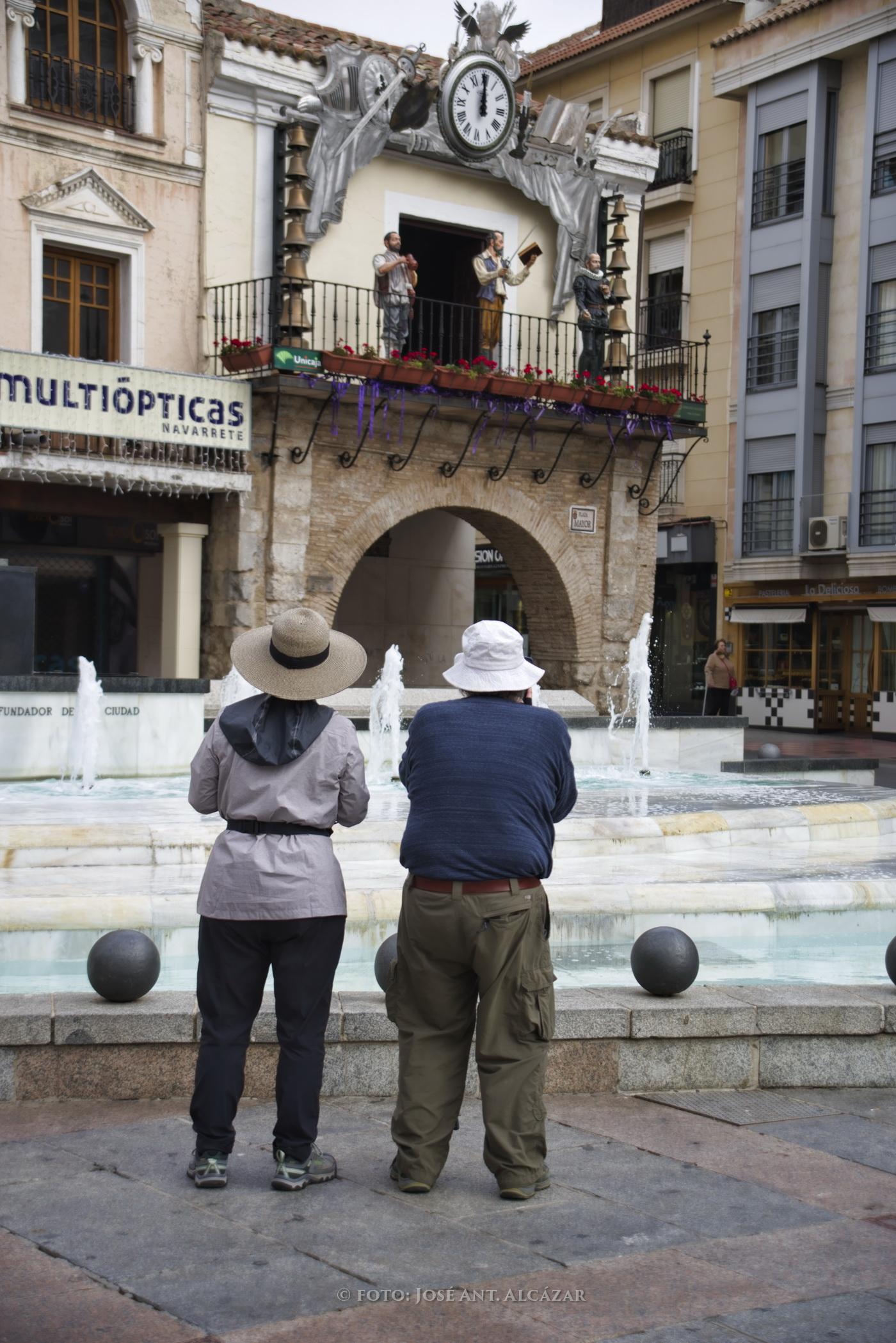 Una pareja de turistas orientales fotografiando el reloj de la Plaza Mayor de Ciudad Real