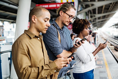 People using smartphones on a train platform