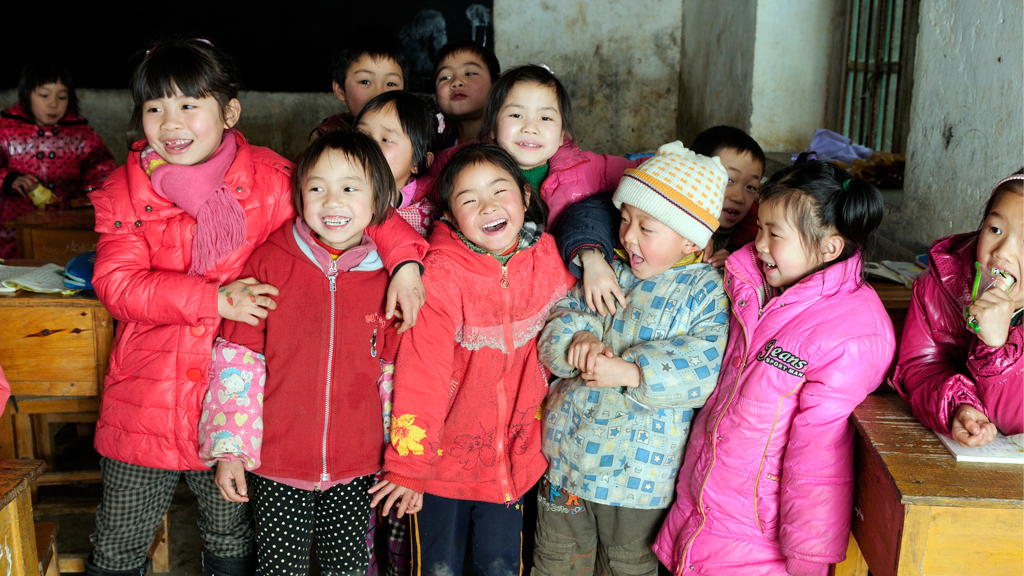 Chinese children gather together laughing.