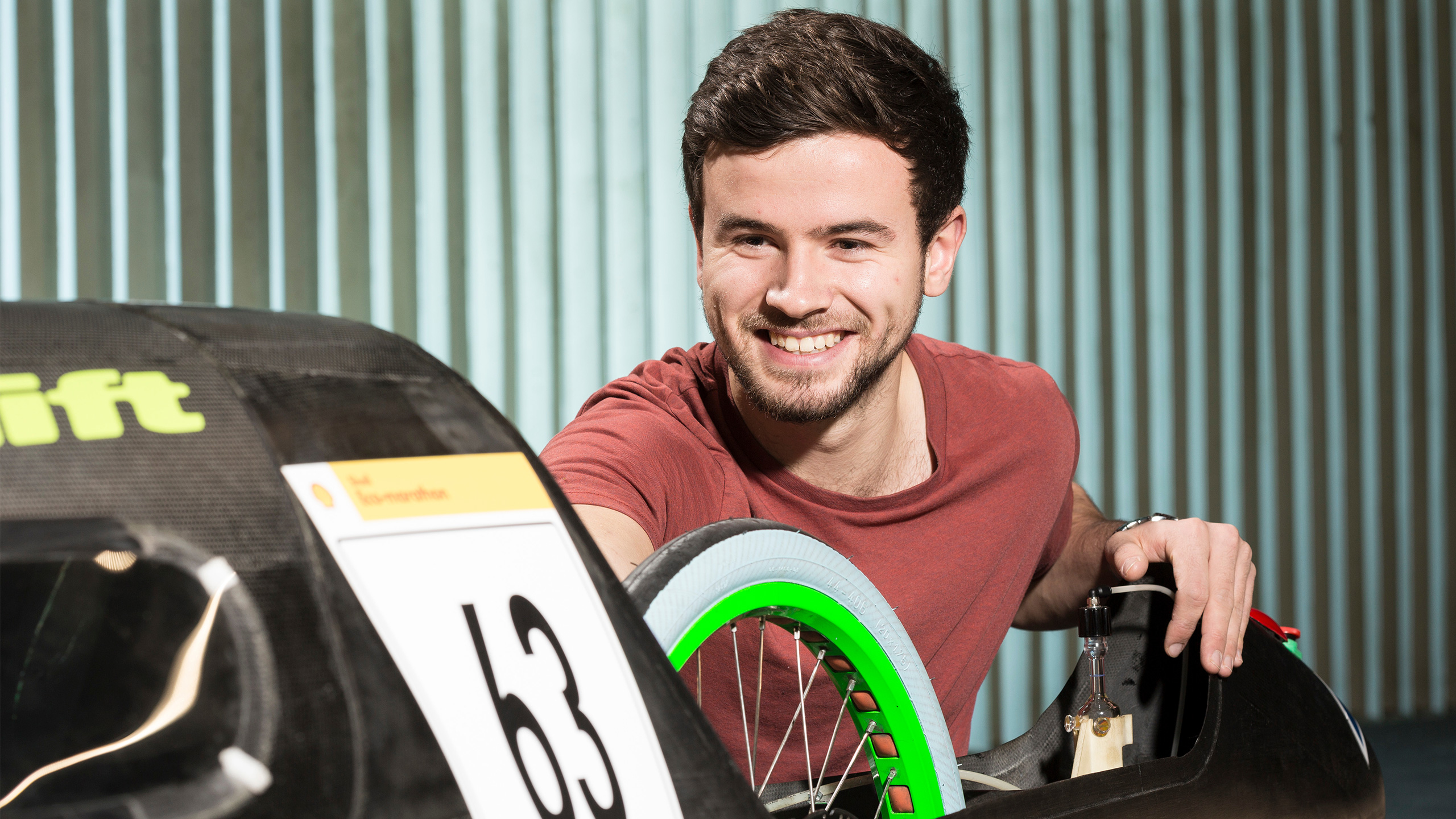 A student smiles as he work on the Green Bath Racing eco-marathon car in our wind tunnel