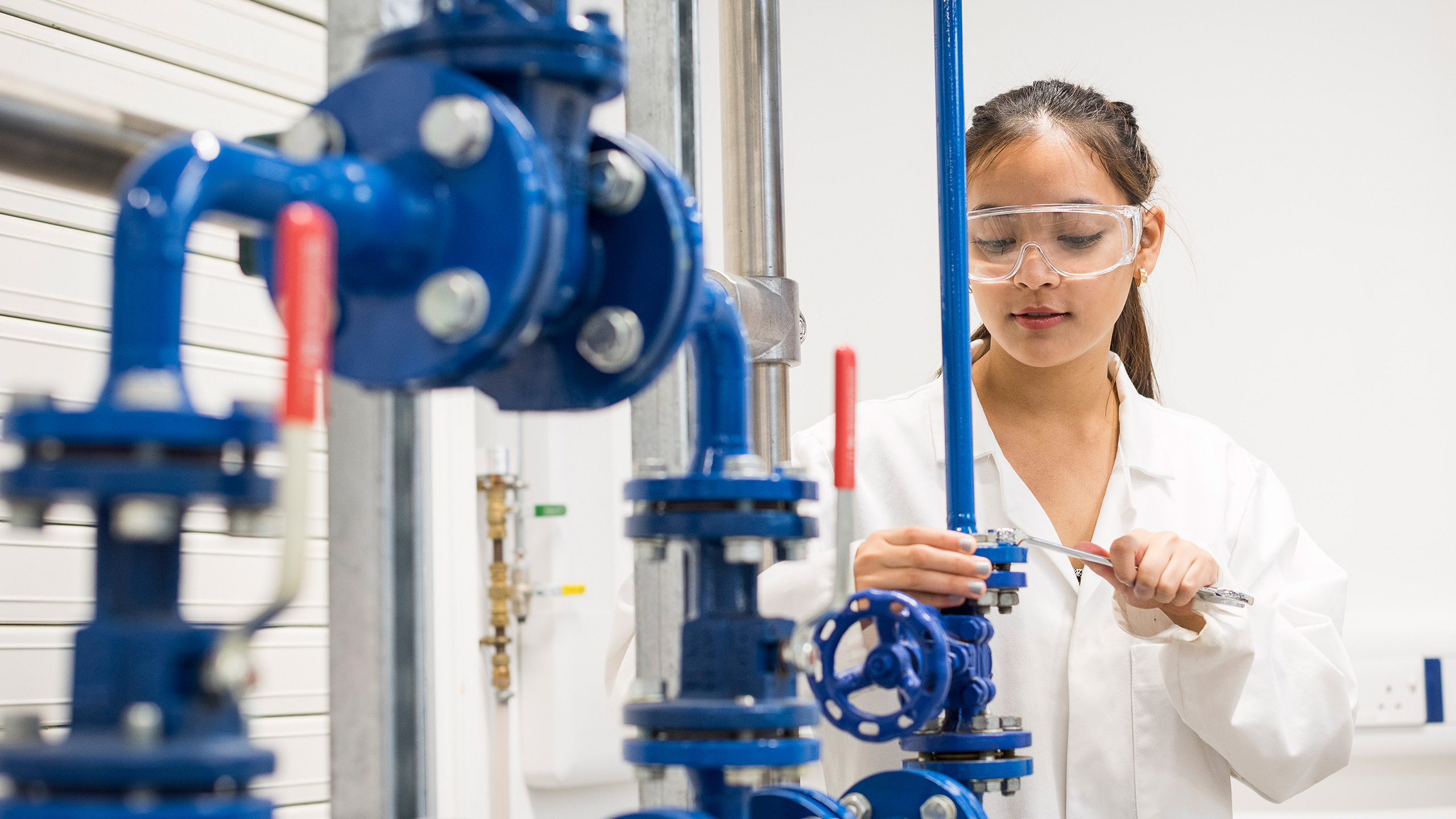 A student examines a rig in our chemical engineering lab.