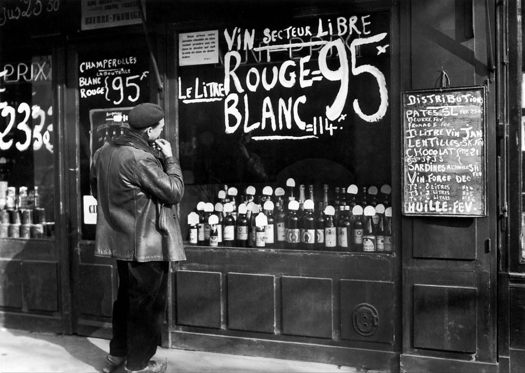 1942. Рабочий читает объявление в витрине магазина бакалейщика