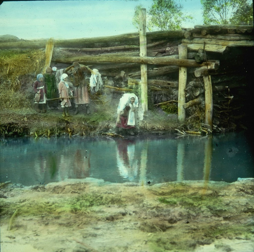 Женщины спускаются под мост к ручью, чтобы постирать белье