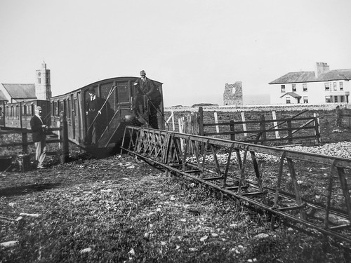 The steps at the end of a carriage to allow the line to be crossed being demonstrated at Ballybunion station with the castle ruins on the right. From Lost Railways from Around the World: Listowel & Ballybunion Railway. Photo: Wikimedia/Creative Commons/ Oliver Wald