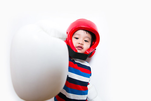 Asian cute boy with white Boxing Gloves and red Head guard on white background