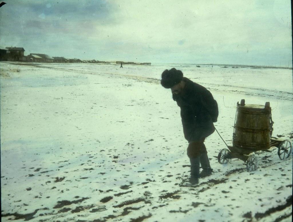 Крестьянин везет бадью с водой по заснеженной дороге