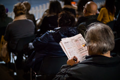 Visitor in the audience playing sudoku at a boring event