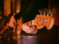 Guitarist playing on a bass guitar