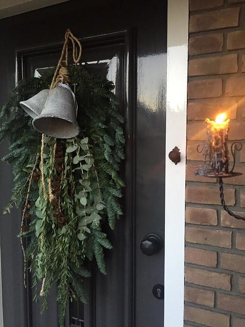 Lange kersttoef met klokken op de voordeur