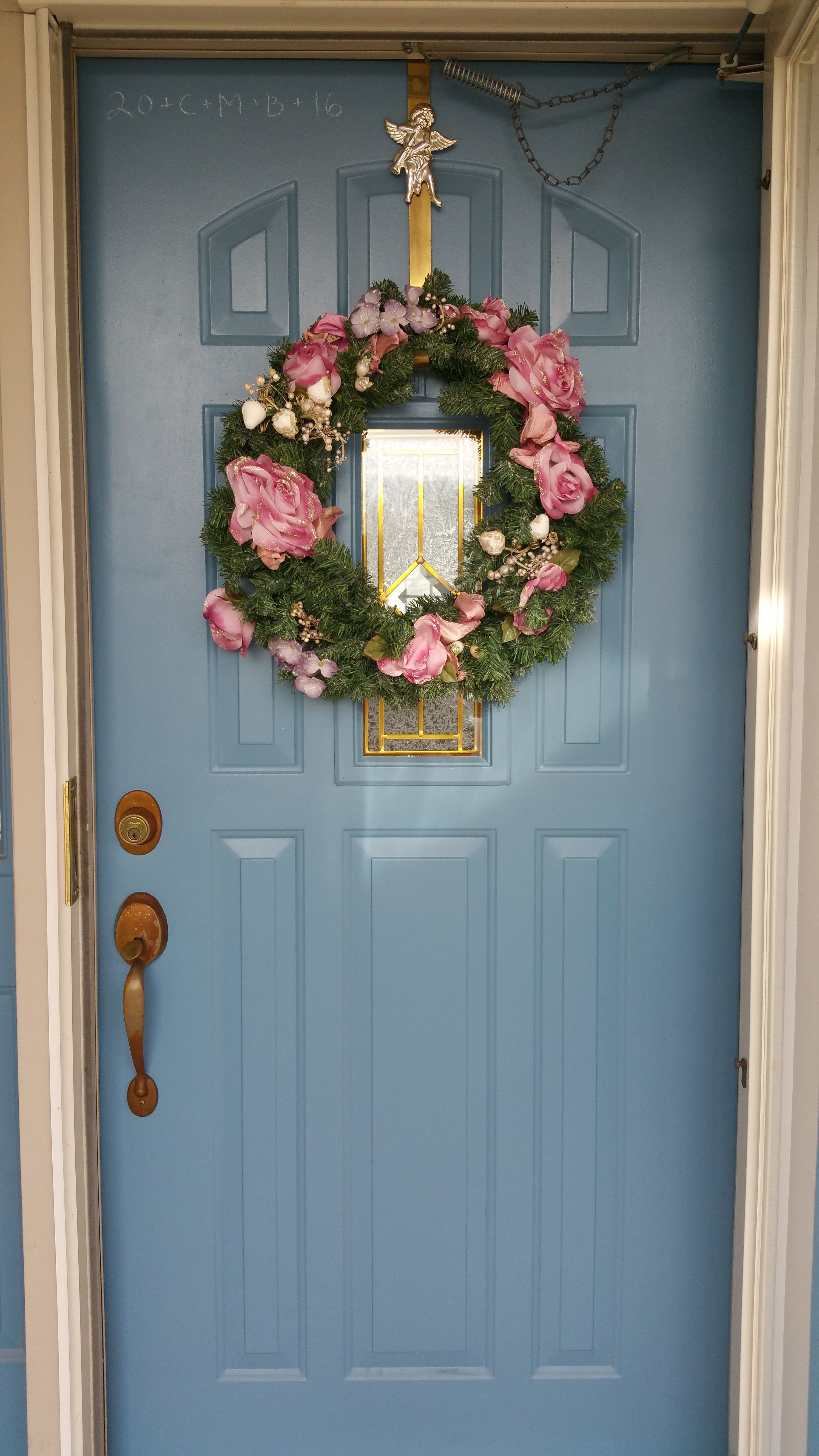 A Christmas wreath adorning an American home, with the door chalked for Epiphanytide and the wreath hanger bearing a placard of the Angel Gabriel.